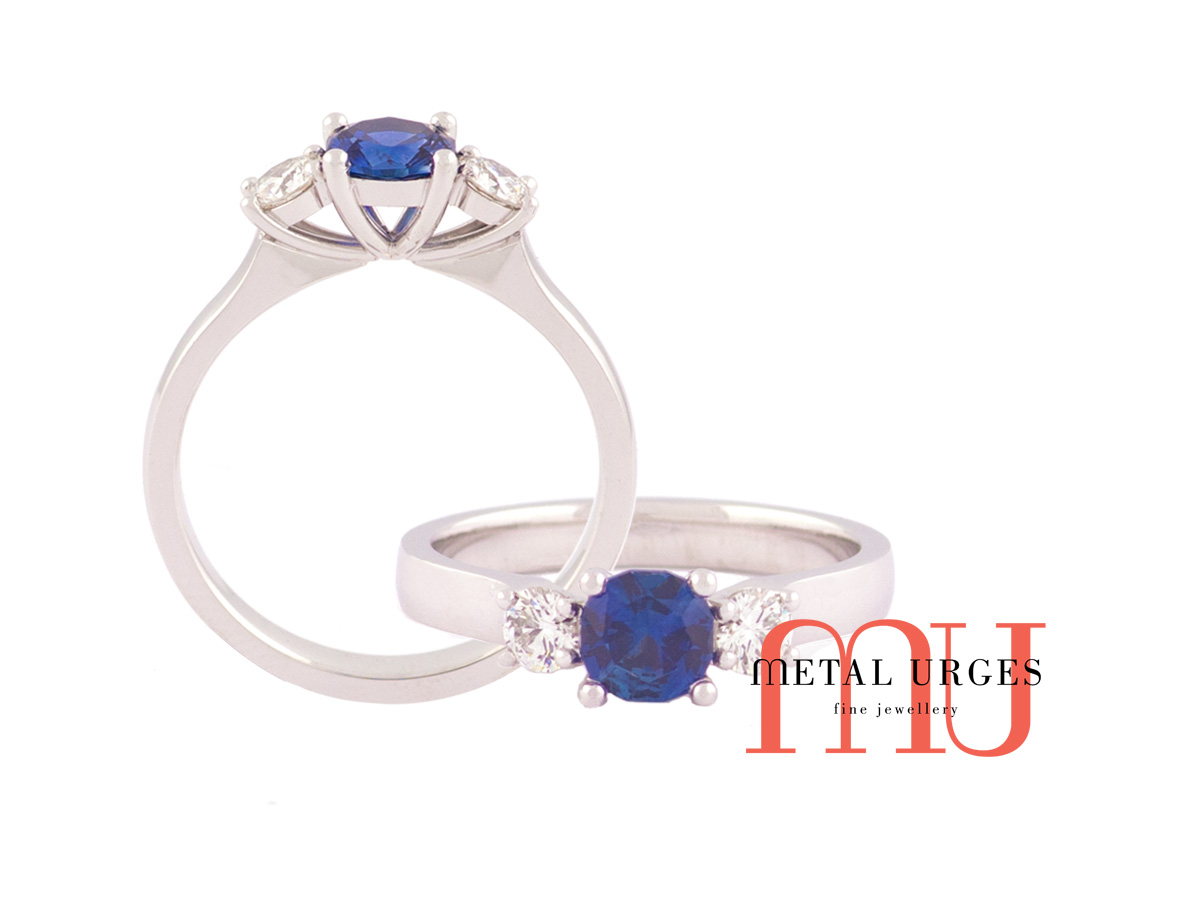Blue natural sapphire, cushion cut, flanked by white diamond set as a 3 solitaire engagement rings