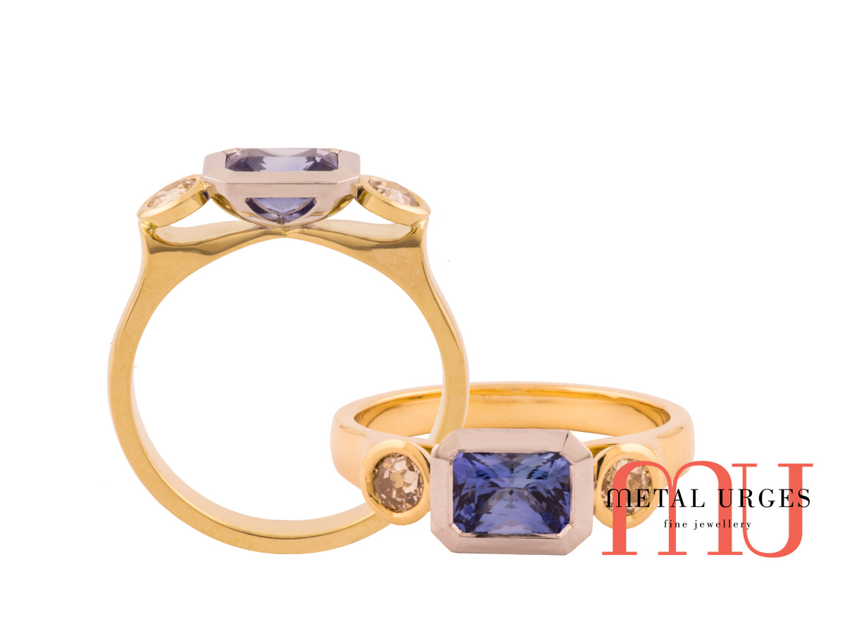 Radiant cut blue sapphire bezel set with two champagne diamonds in 18ct yellow gold