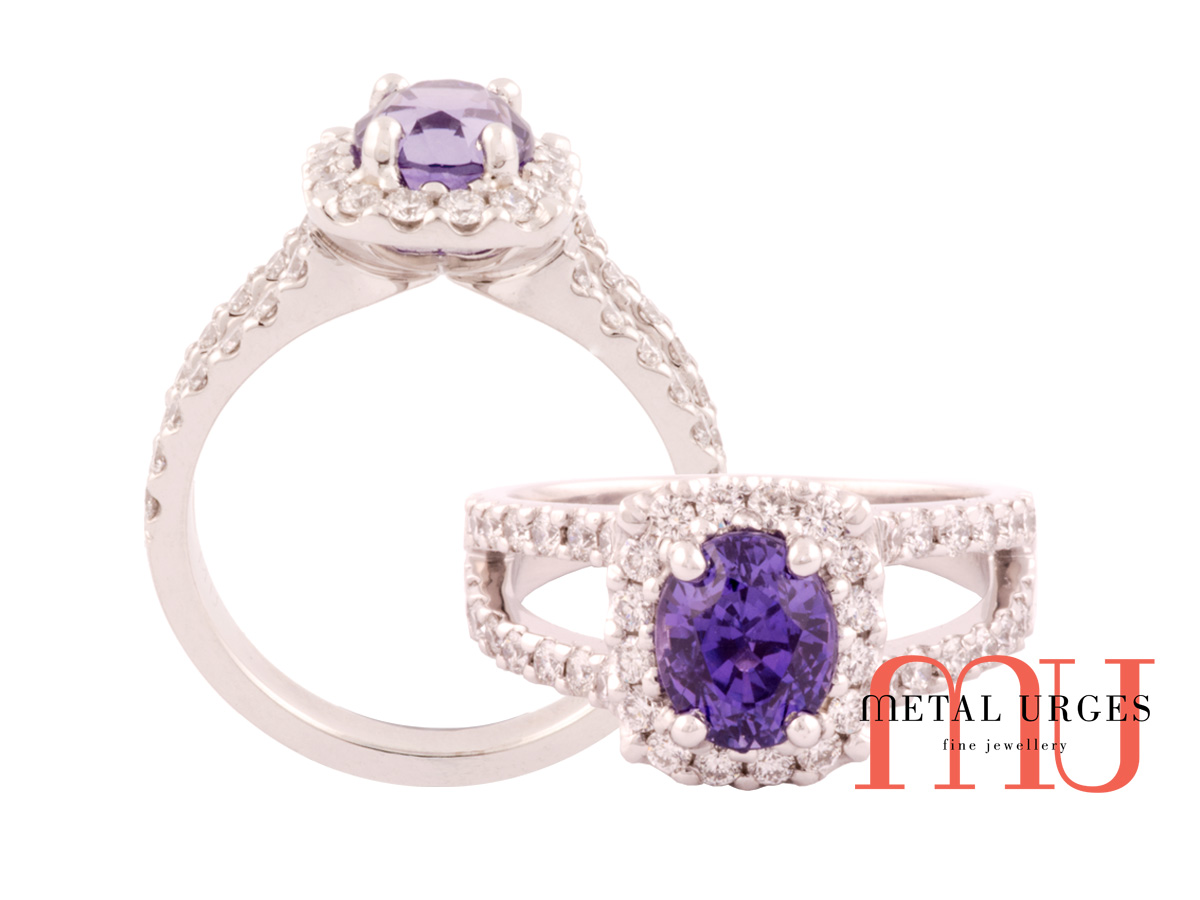 Purple oval sapphire surrounded by diamonds in split shank.