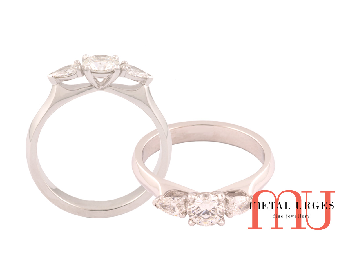 Trilogy ring of round and pear diamonds claw set in platinum.