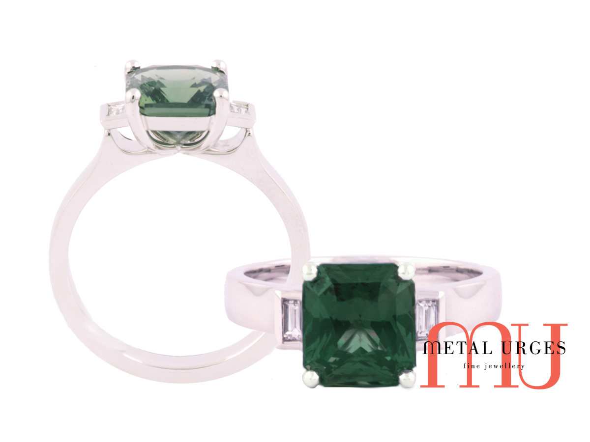 Green sapphire and baguette white diamond engagement ring in platinum