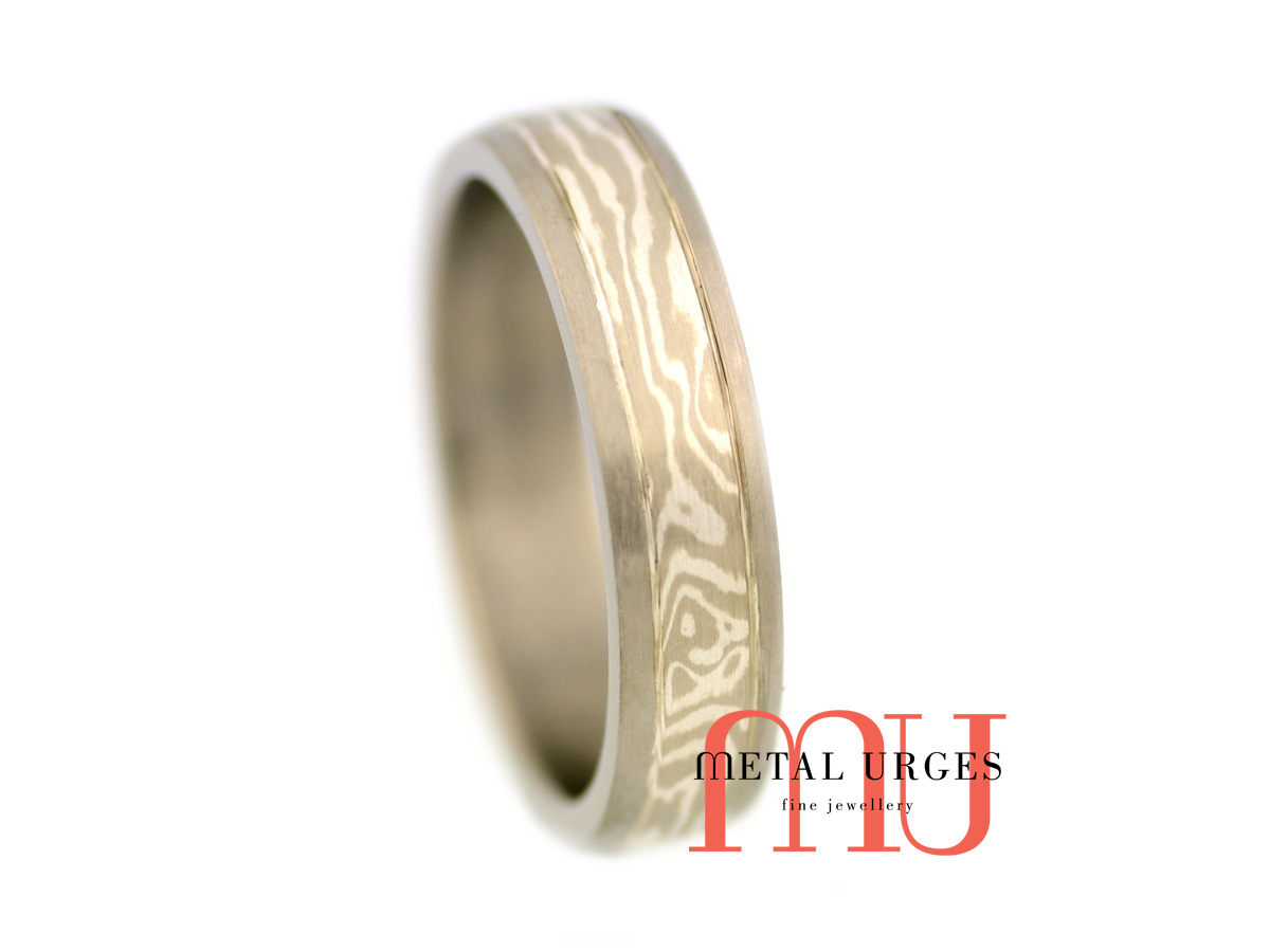 Titanium wedding ring with a central 18ct white gold and silver Mokume Gane feature. Custom made in Australia.