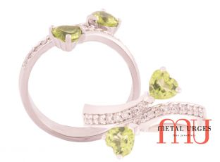 Heart cut peridot set in 18ct white gold grain set diamond bypass ring.