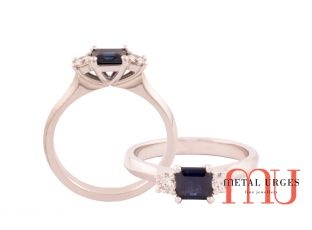 Princess cut blue sapphire claw set ring with side white diamonds
