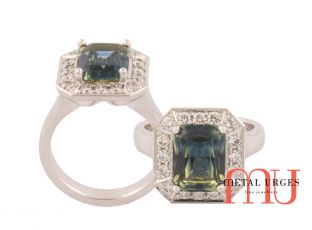 Radiant cut green sapphire with modern cluster set diamonds in 18ct white gold