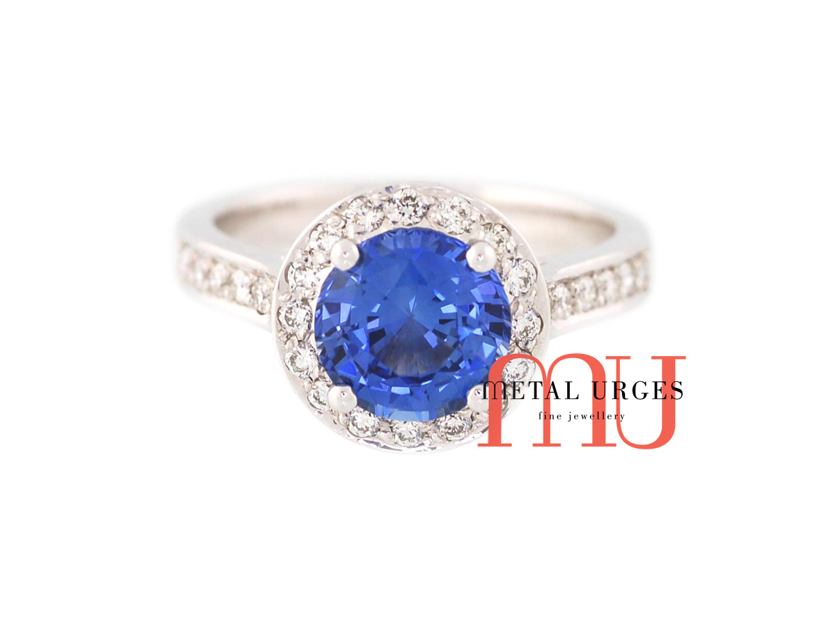 Vibrant blue sapphire and round white diamond modern cluster engagement ring in 18ct white gold. Custom made in Australia.