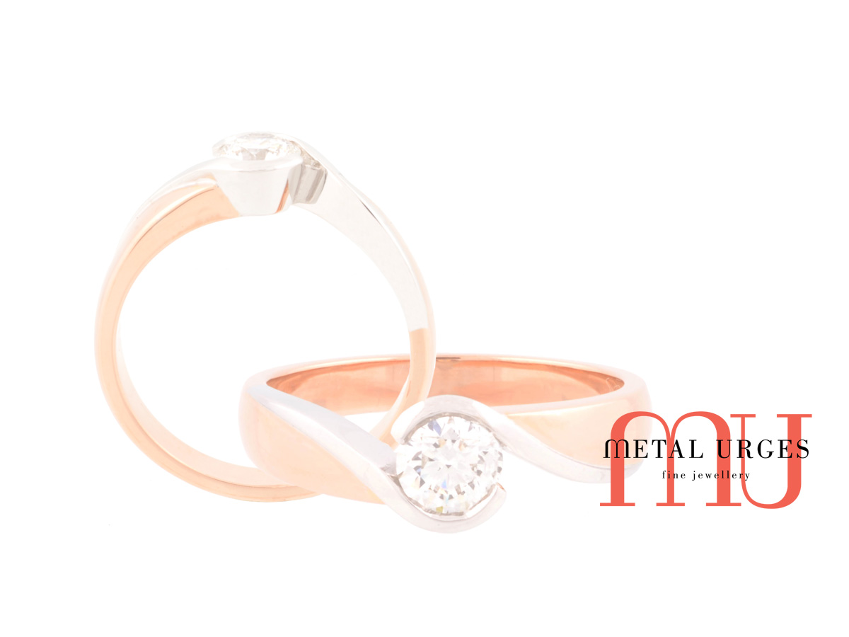 Solitaire 18ct rose gold and white gold GIA certified round white diamond engagement ring with curved and sweeping features.