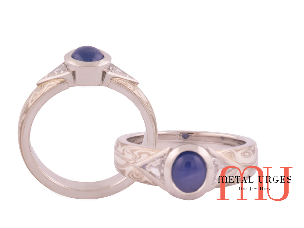Cabochon natural sapphire with triangular diamonds and mokume gane inlay.