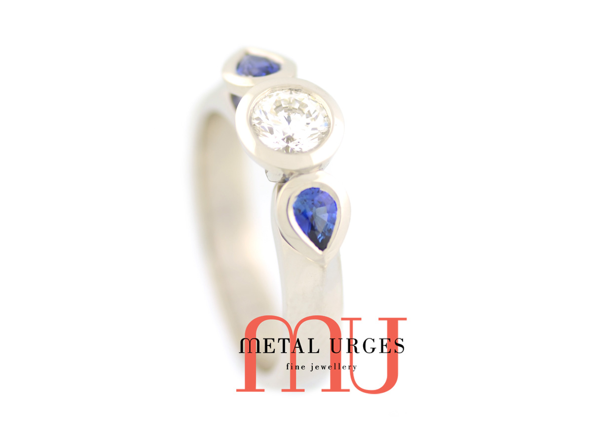 18ct white gold bezel set, natural round white diamond with two tear drop bezel set blue Sri Lankan sapphires either side. Custom made in Australia.